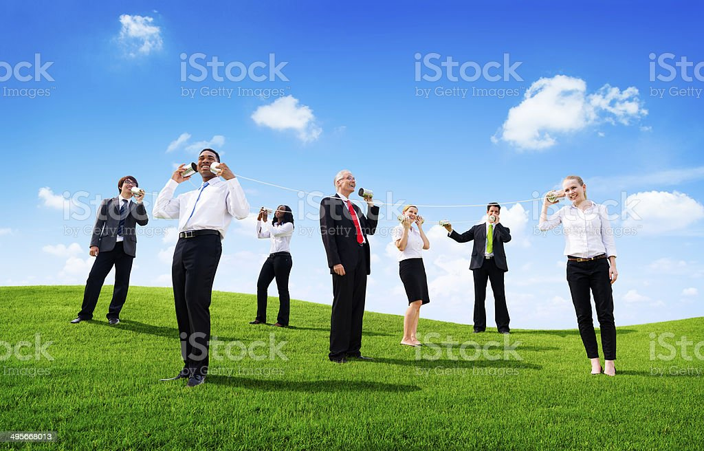 Business People Outdoors Talking through Tin Can Phone stock photo