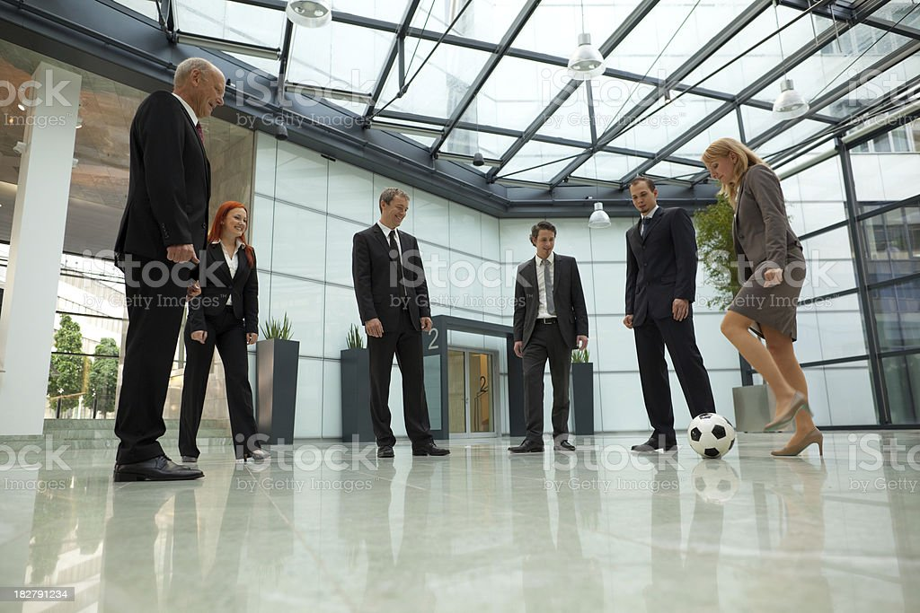 business people playing soccer in lobby royalty-free stock photo