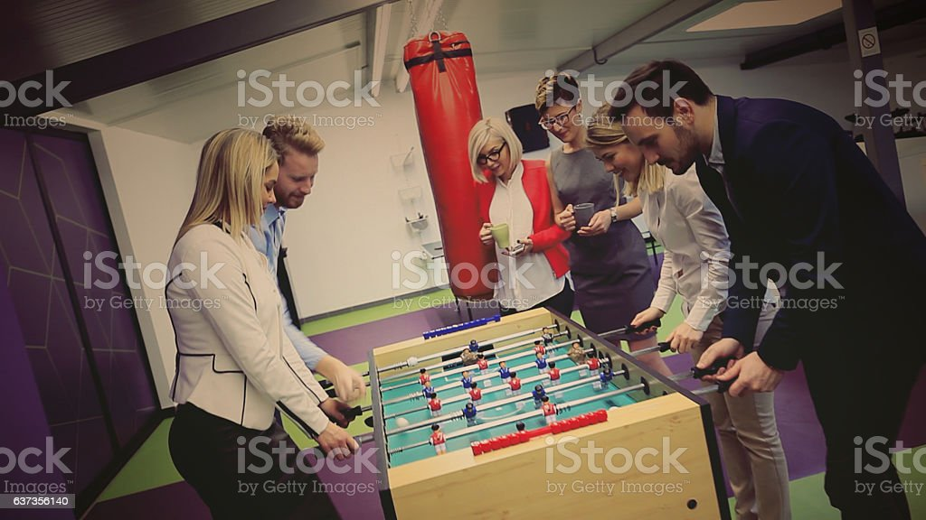 business people playing table soccer stock photo