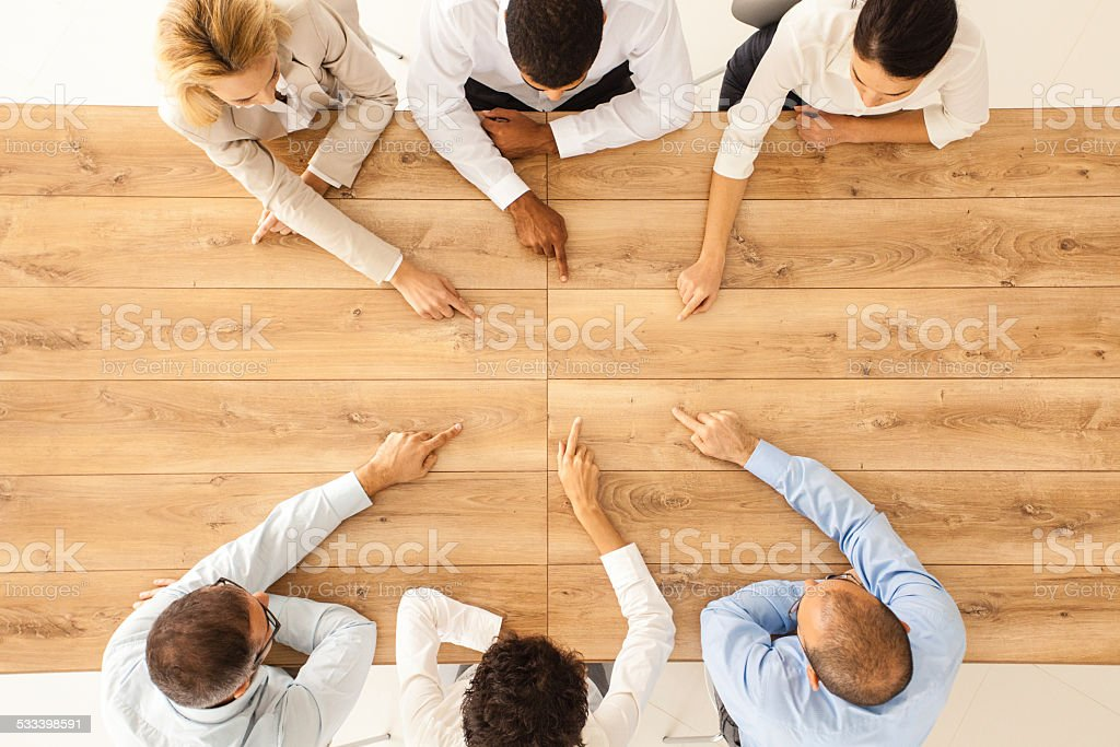Business people pointing at empty office table stock photo