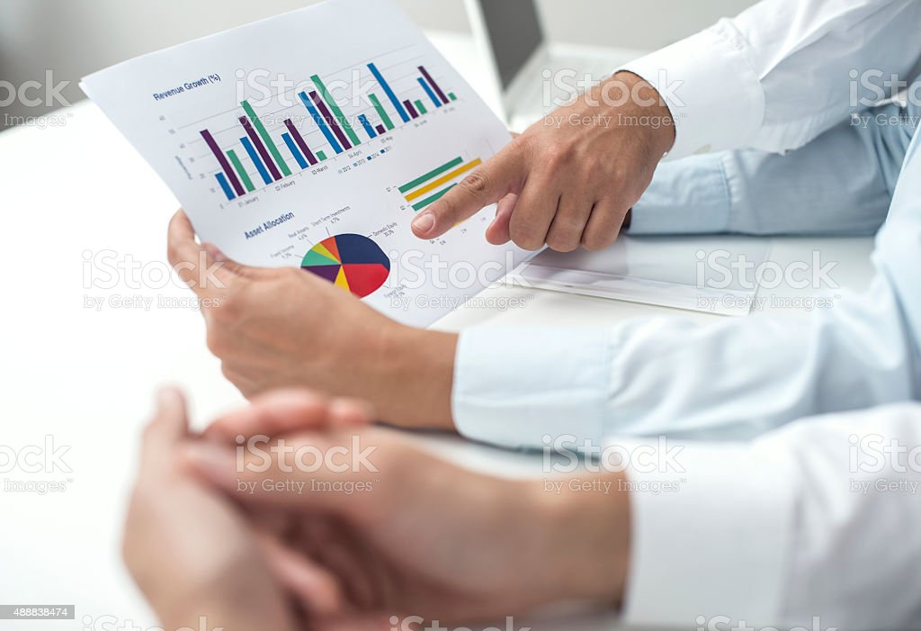 Business People Pointing At Graph In Meeting stock photo