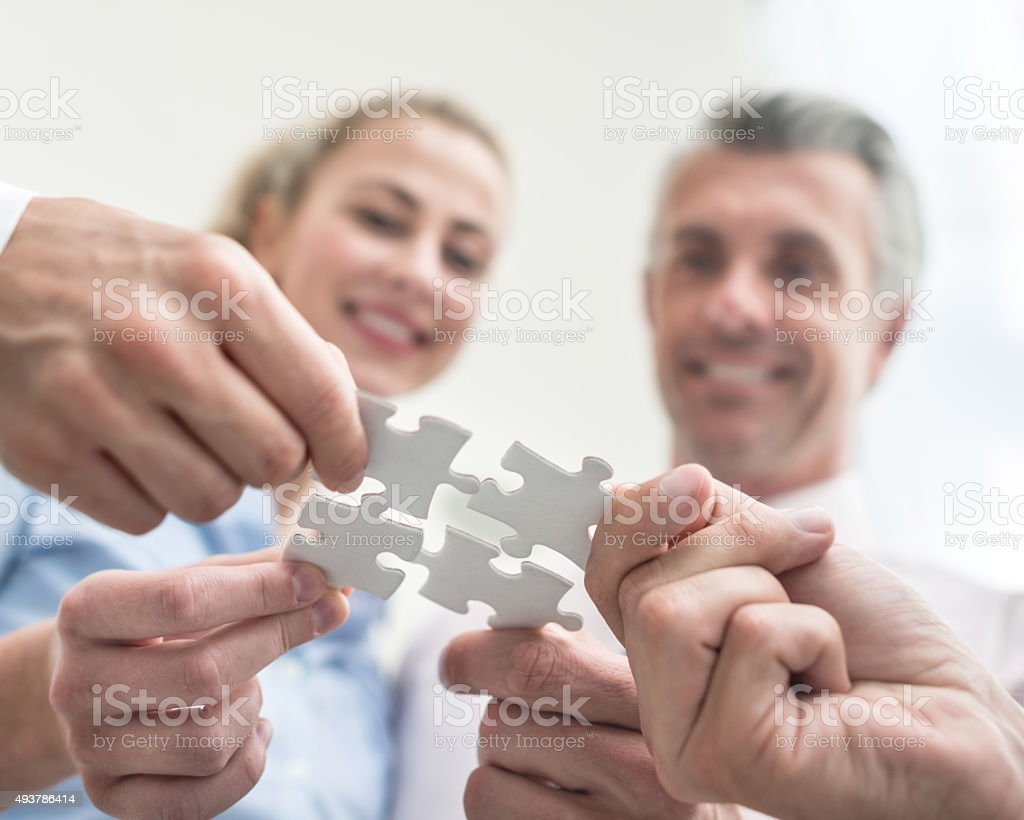 Business people putting pieces of a puzzle together stock photo
