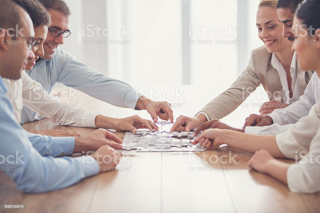 Business people putting together jigsaw puzzle stock photo