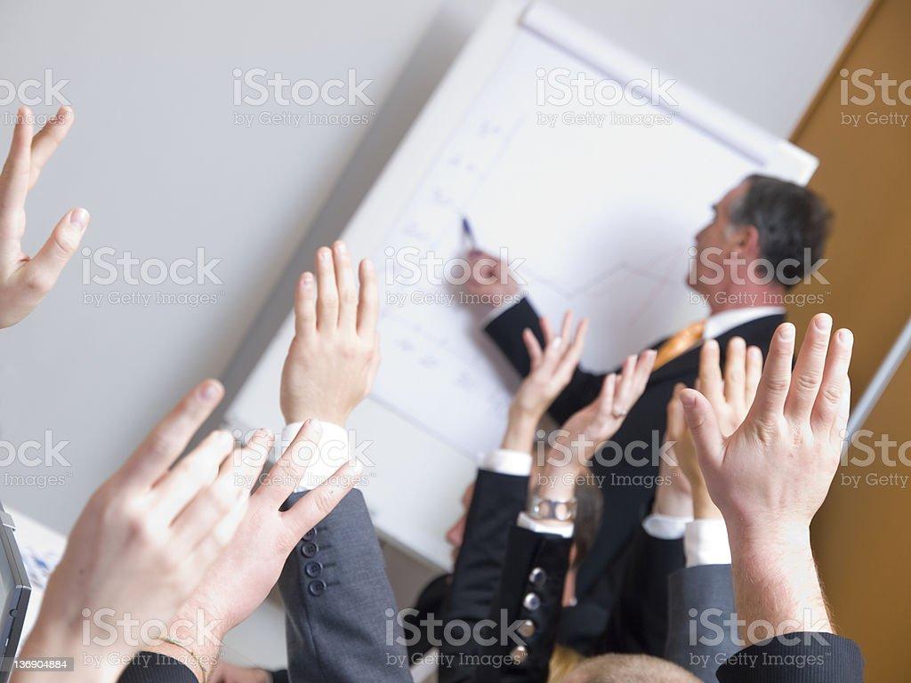Business people raising hands at a seminar royalty-free stock photo