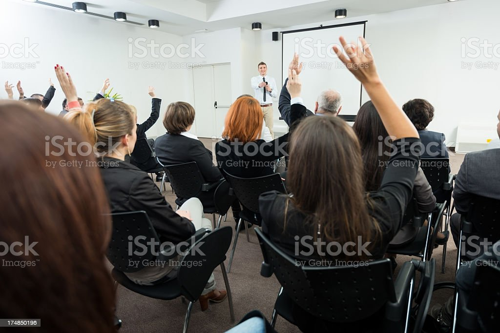 Business people raising hands in seminar royalty-free stock photo