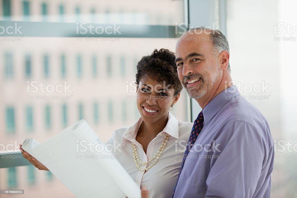 Business people reading blueprints in office royalty-free stock photo