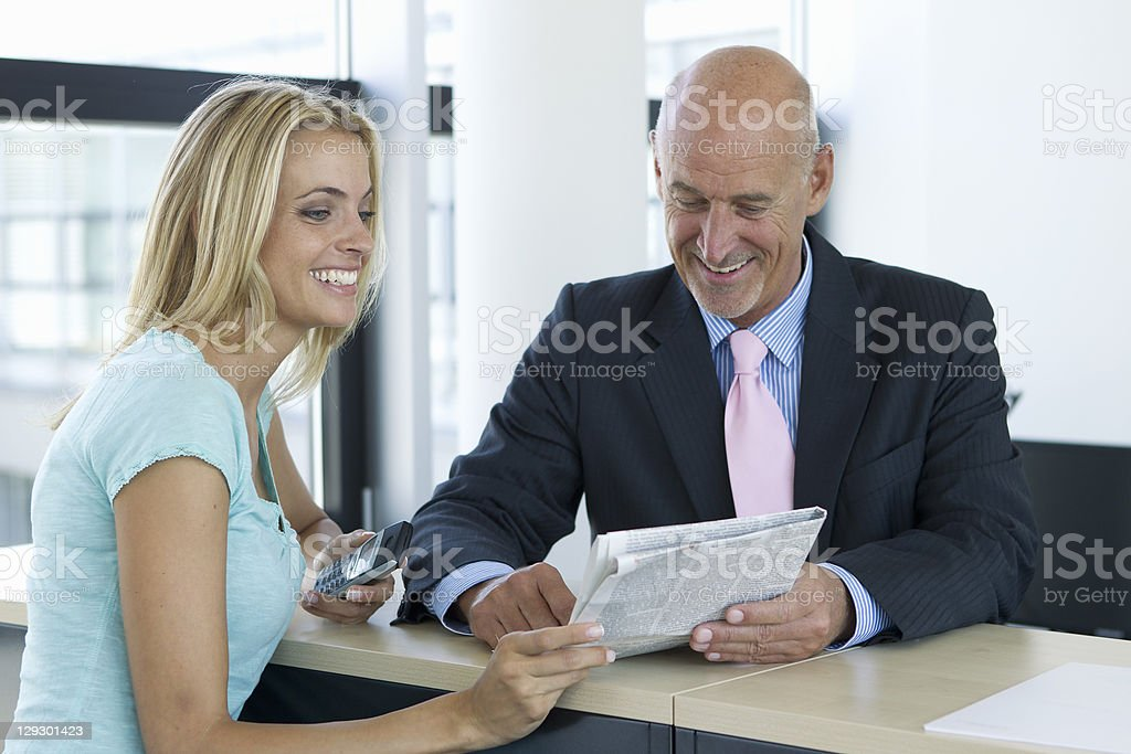 Business people reading newspaper royalty-free stock photo