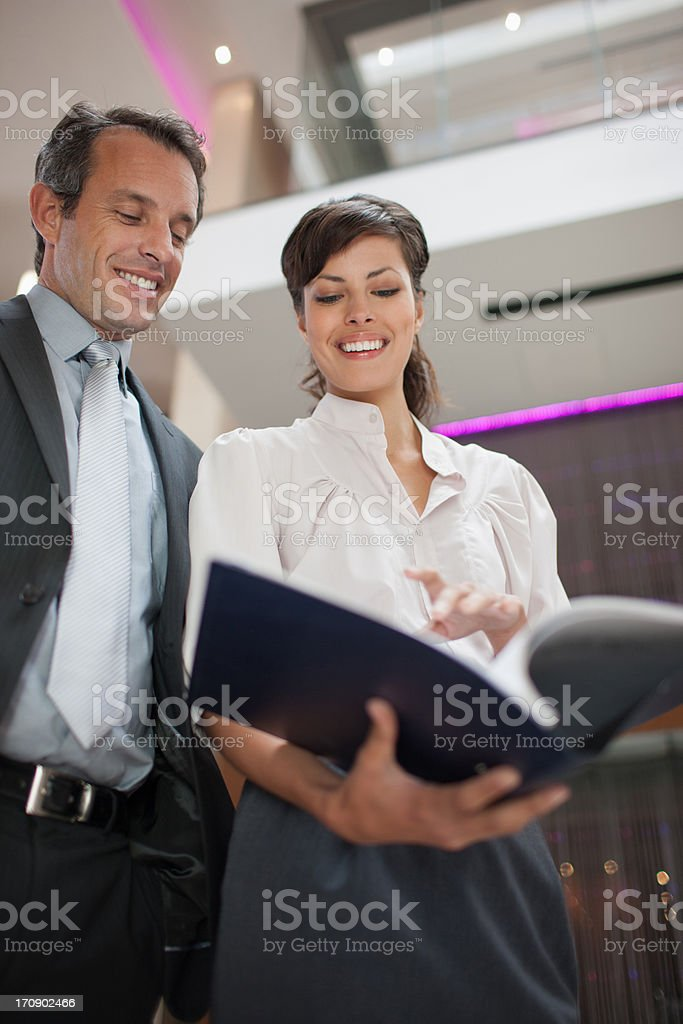 Business people reading report in lobby royalty-free stock photo