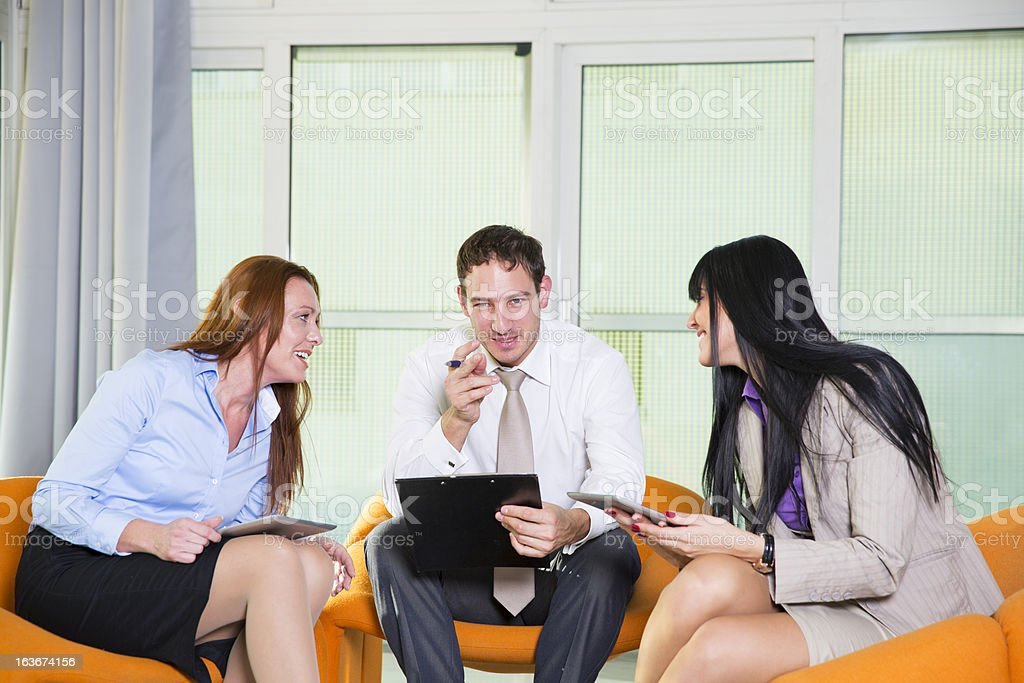 Business people relaxing...chatting and smiling in a brainstorming room royalty-free stock photo