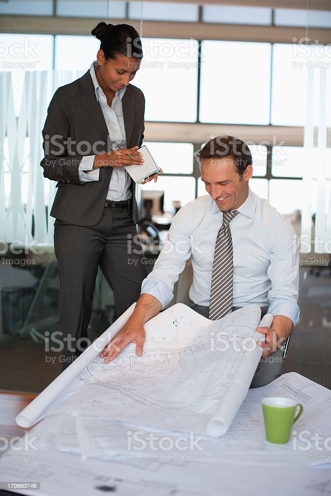 Business people reviewing blueprints together in office stock photo