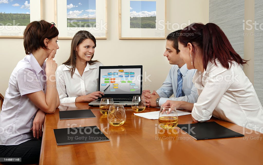 Business people reviewing laptop screen with wine royalty-free stock photo