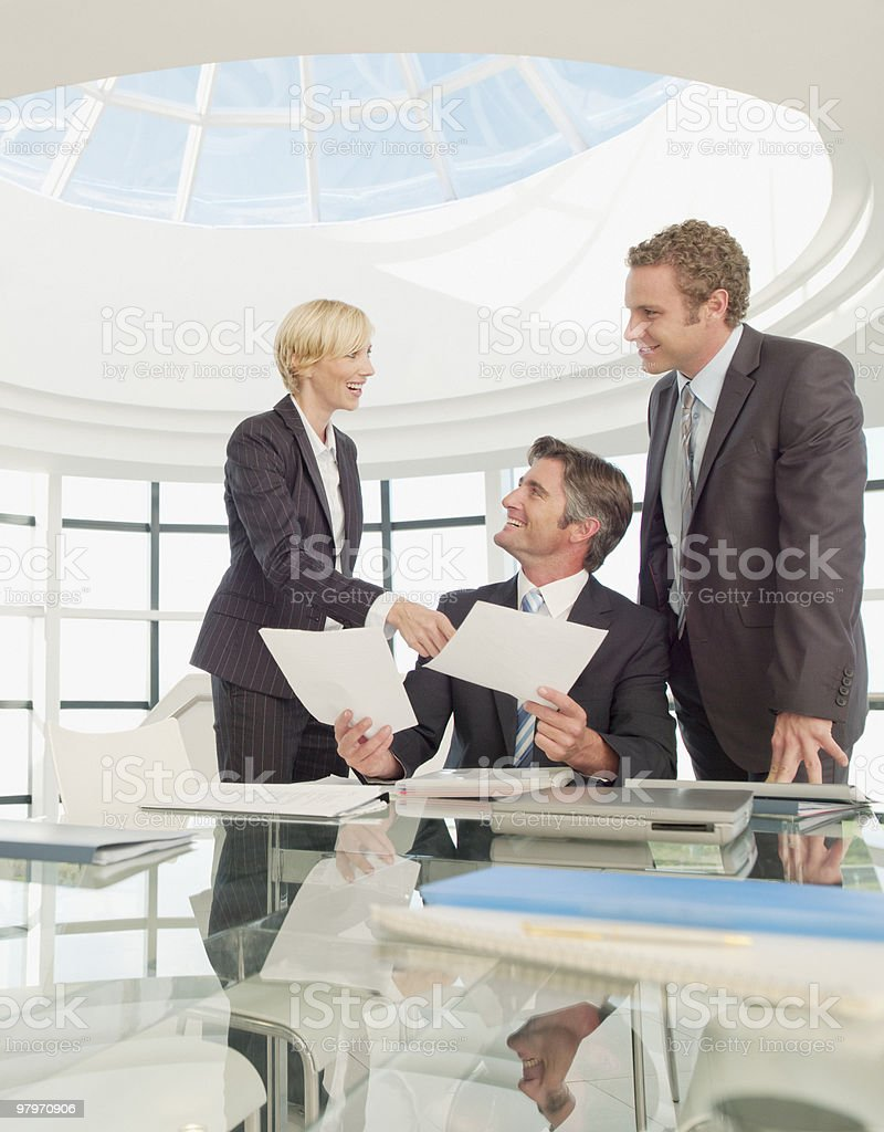 Business people reviewing paperwork in modern office royalty-free stock photo