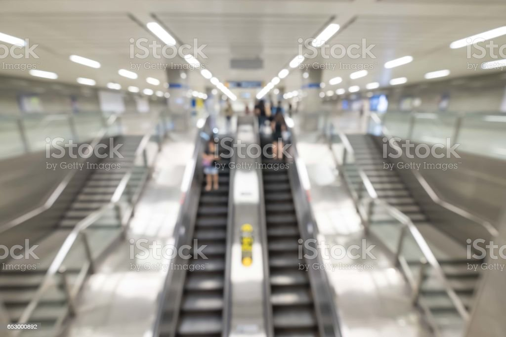 business people rushing on the escalator in motion blur on the subway station. stock photo