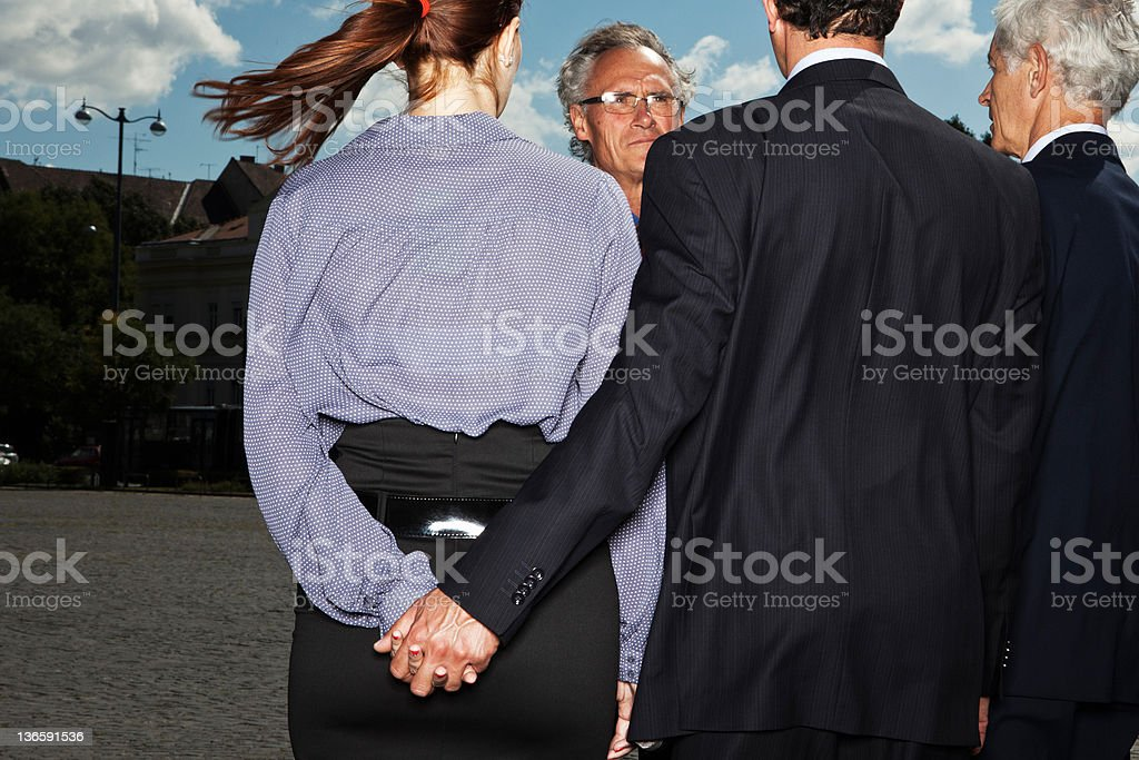 Business people secretly holding hands stock photo