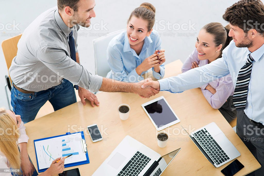 Business people shaking hands across table stock photo