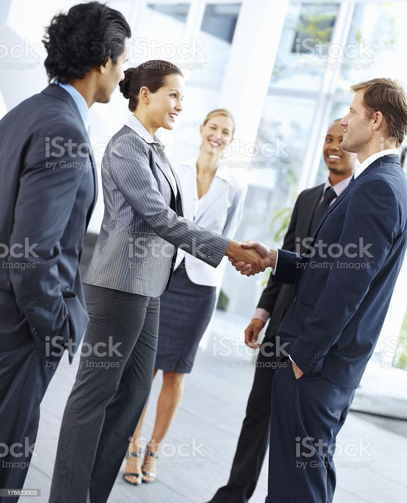 Business people shaking hands and smiling in suits stock photo