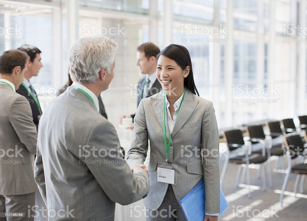Business people shaking hands at seminar stock photo