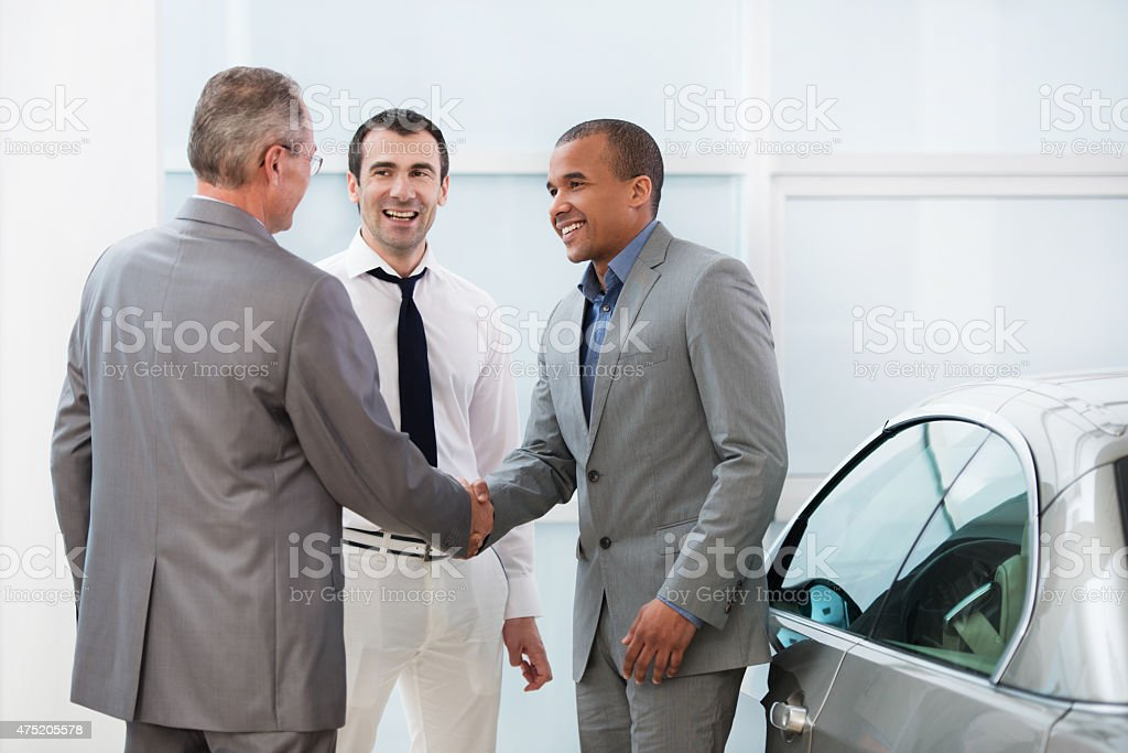 Business people shaking hands in a car showroom. stock photo