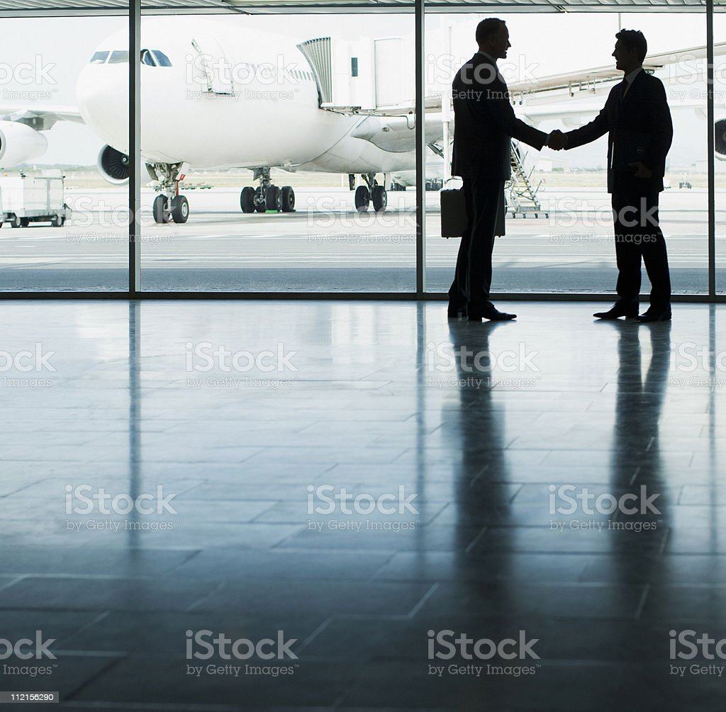 Business people shaking hands in airport royalty-free stock photo