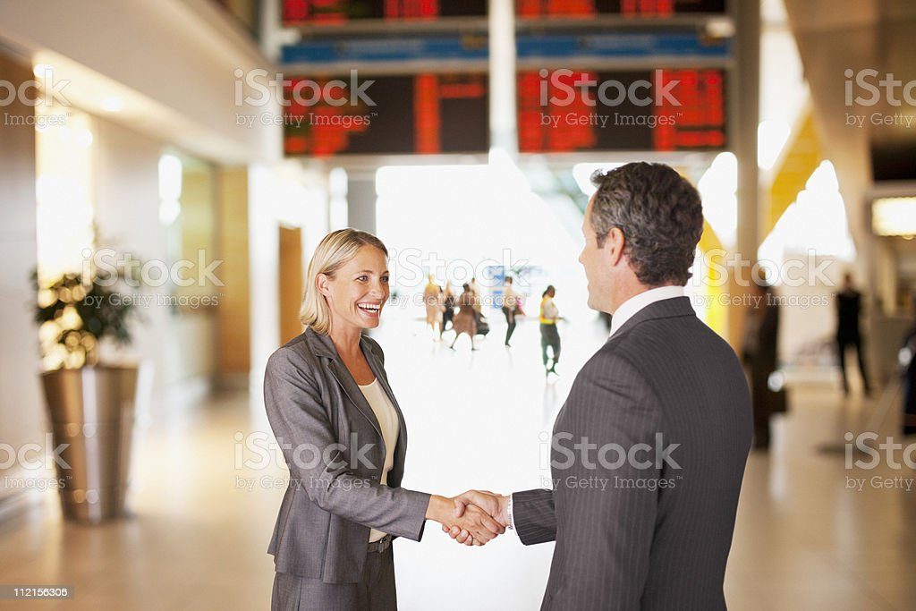 Business people shaking hands in airport stock photo