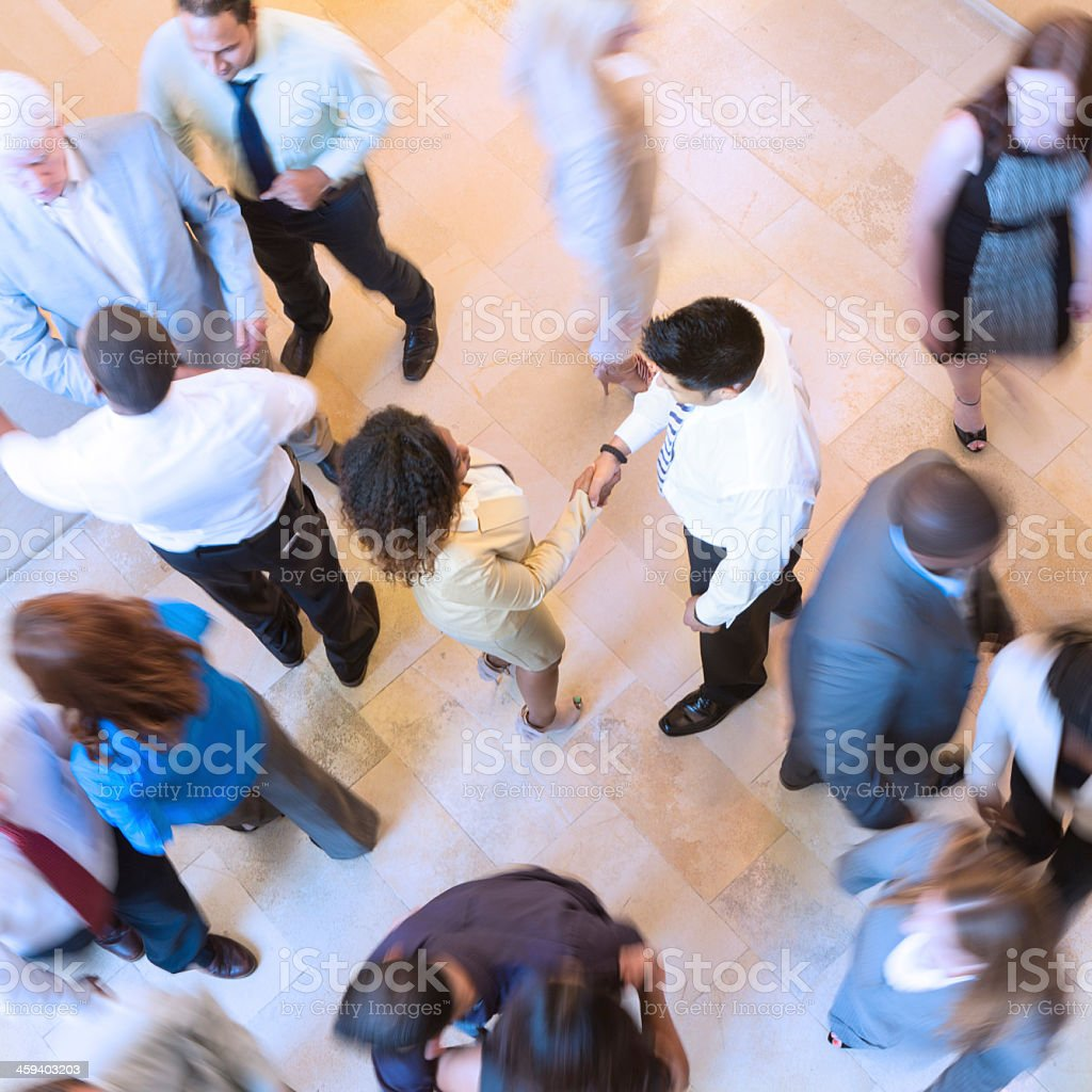 Business people shaking hands in busy crowded lobby stock photo
