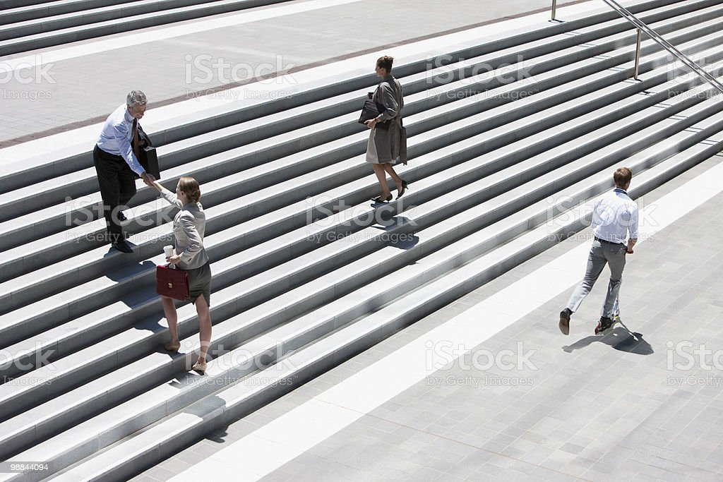 Business people shaking hands on steps outdoors stock photo