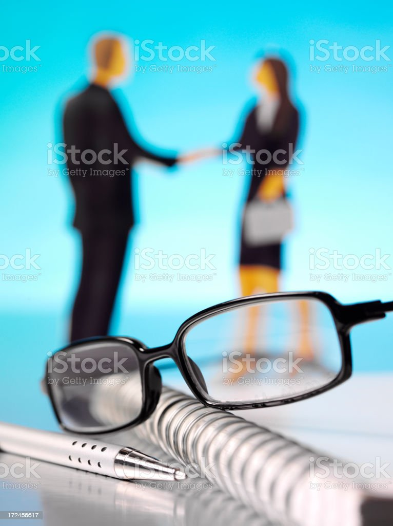 Business People Shaking Hands with Reading Glasses and Stationery royalty-free stock photo