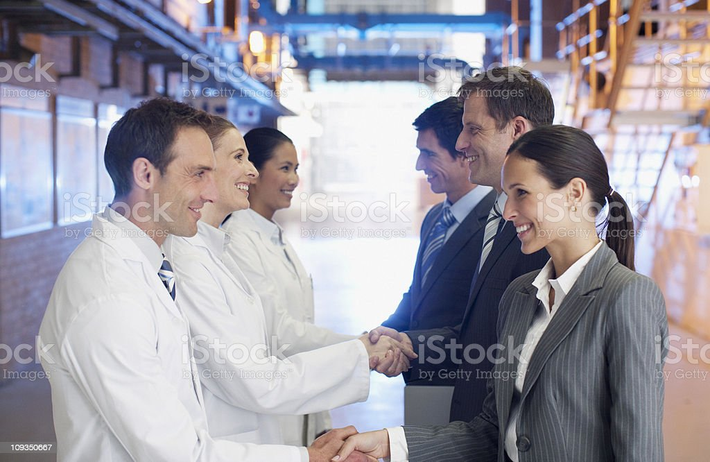 Business people shaking hands with scientists in factory royalty-free stock photo