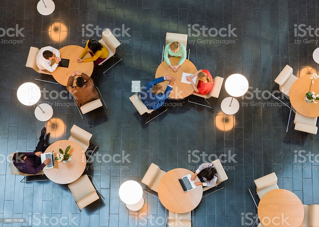 Business people sitting at tables in office lobby stock photo