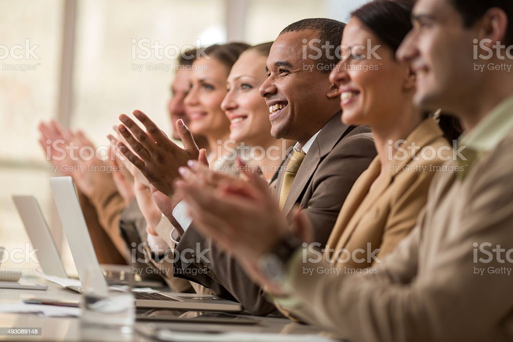 Business people sitting in a row and applauding. stock photo