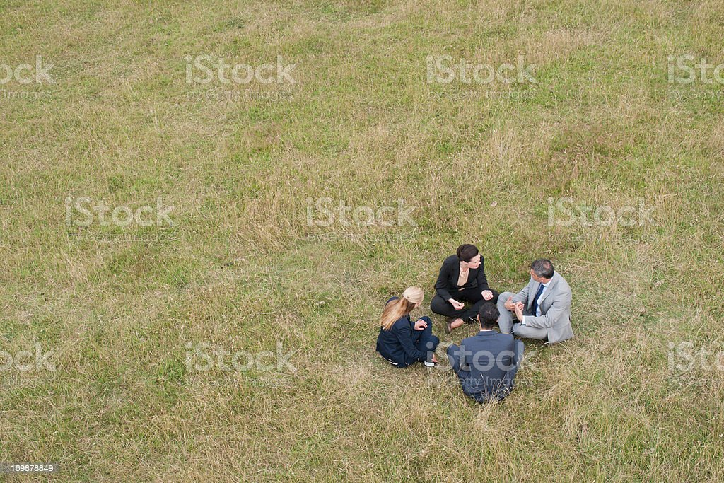 Business people sitting in grass together outdoors royalty-free stock photo