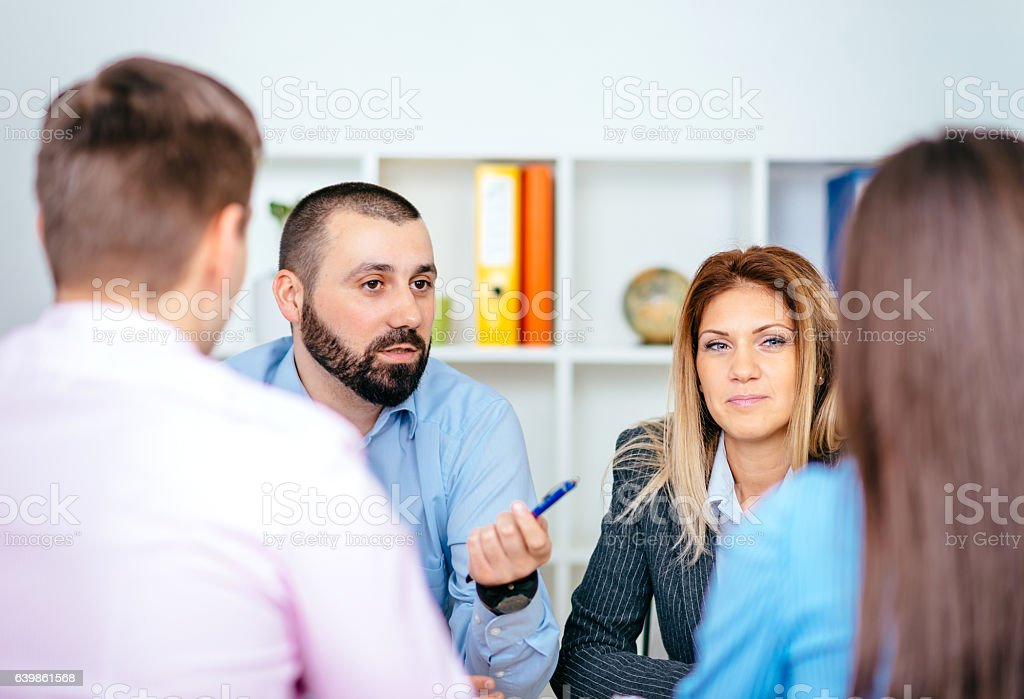 Business people sitting in office and discussing investments stock photo