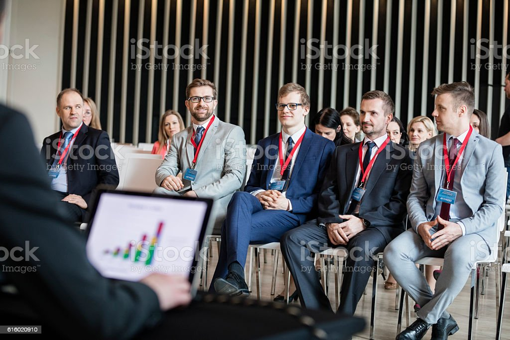 Business people sitting in seminar hall stock photo