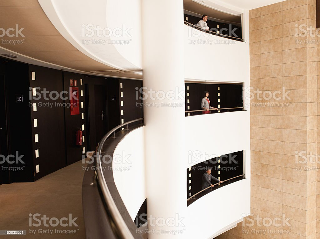 Business people standing at balcony in atrium stock photo