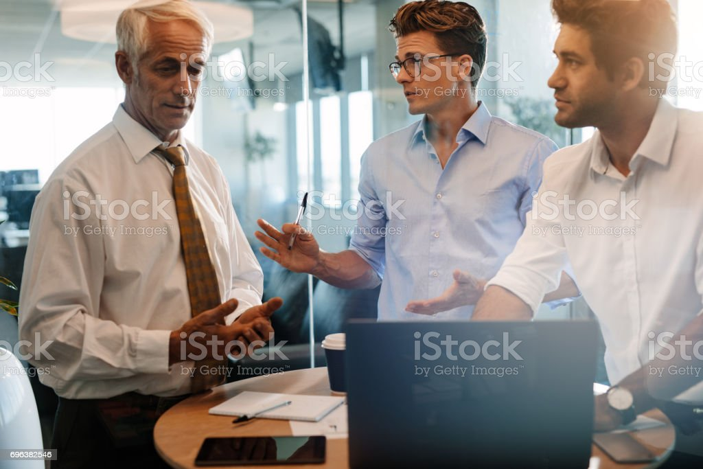 Business people standing at the table and discussing stock photo