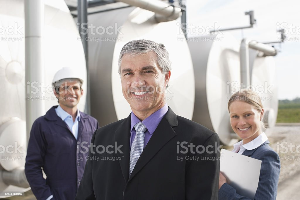Business people standing beside tanks outdoors royalty-free stock photo