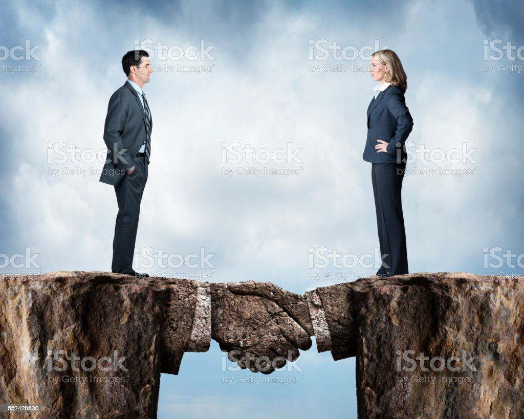 Business People Standing On Opposite Cliffs Joined By Handshake stock photo
