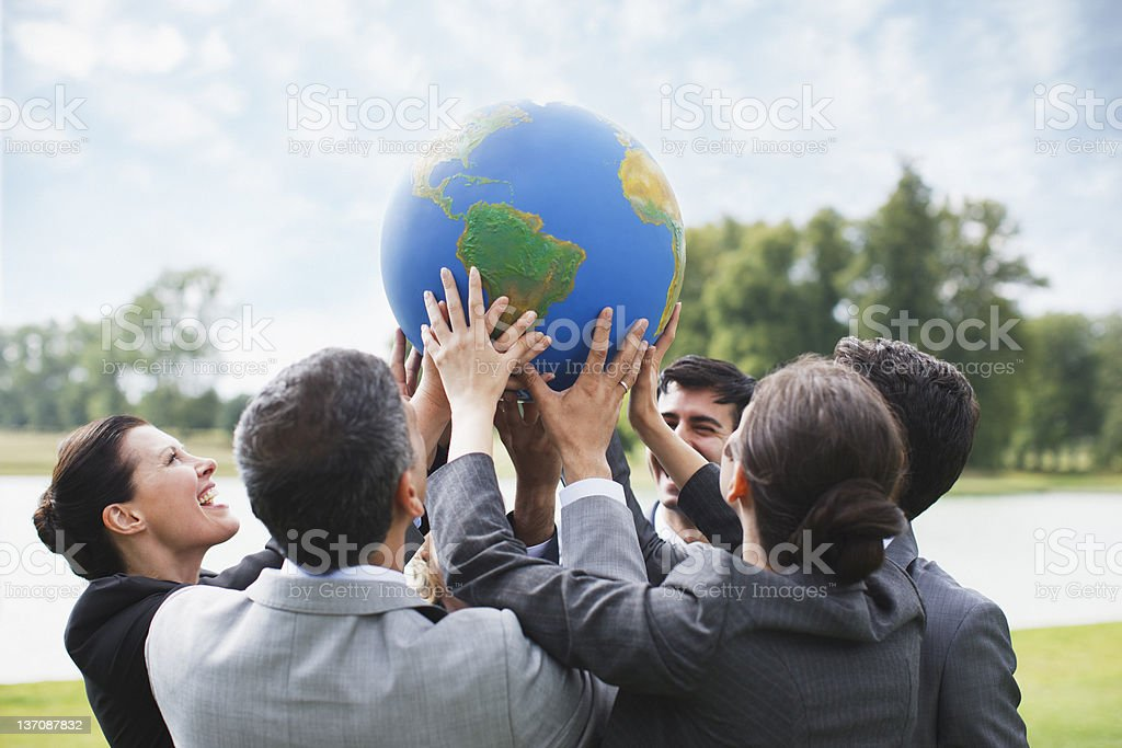 Business people standing outdoors holding globe together stock photo