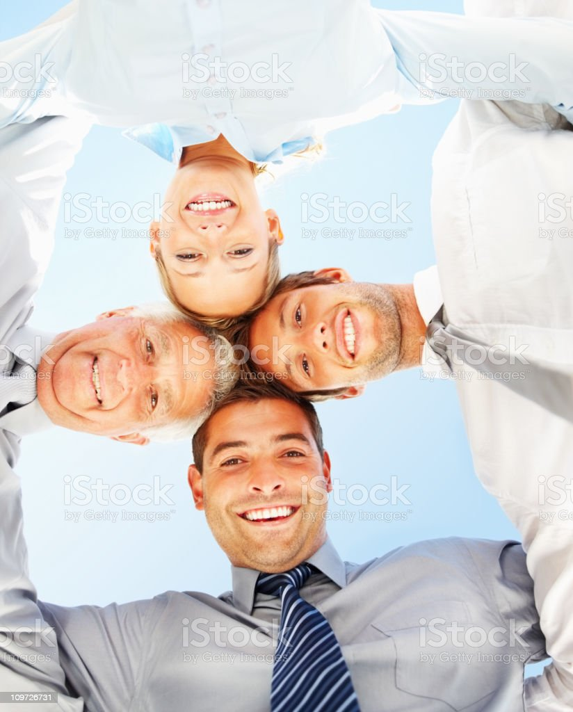 Business people standing together in a huddle and smiling royalty-free stock photo