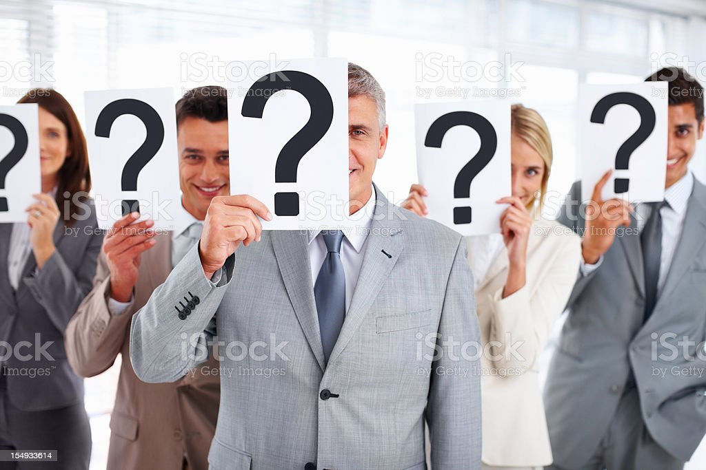 Business people standing with question mark on boards royalty-free stock photo