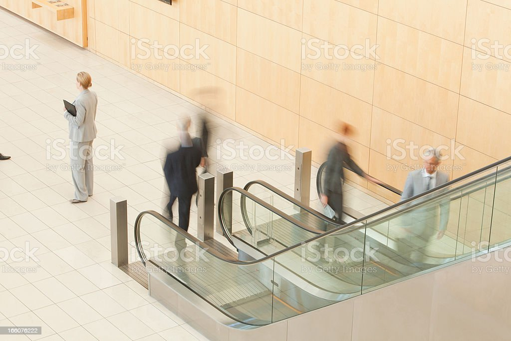 Business people stepping off escalator royalty-free stock photo