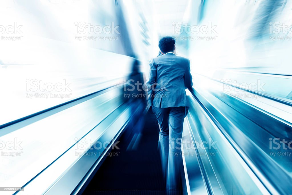 business people taking escalator blur motion,business on the move stock photo