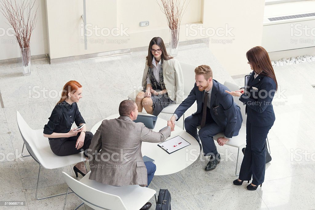 Business people talking and shaking hands shot from above stock photo