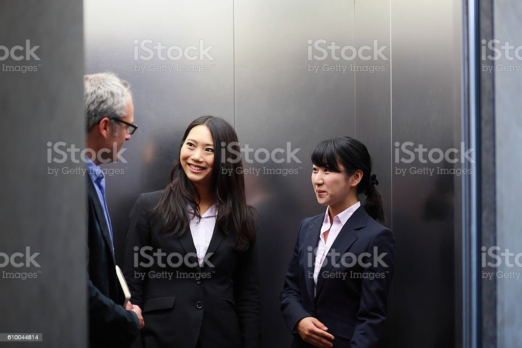 business people talking in office elevator stock photo