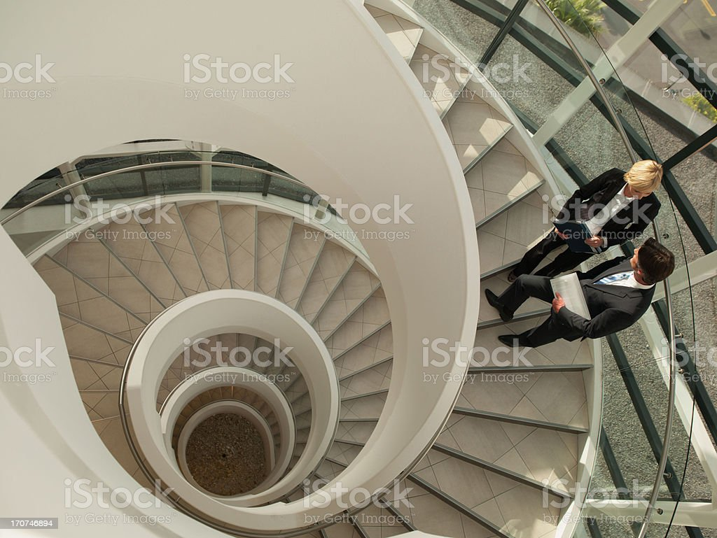 Business people talking on circular staircase stock photo