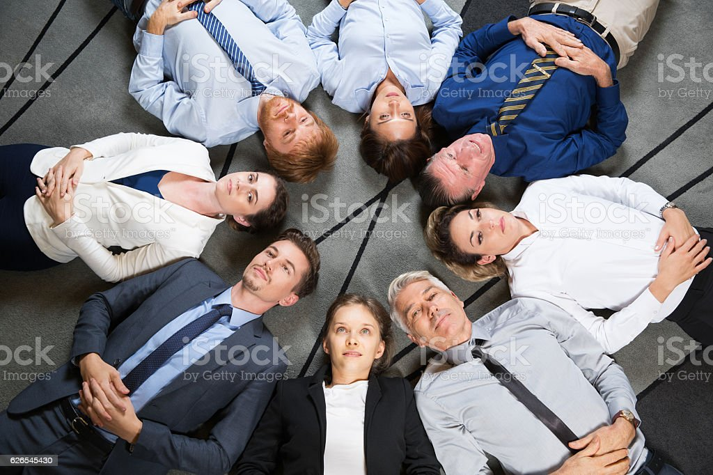Business People Team Resting on Floor in Circle stock photo