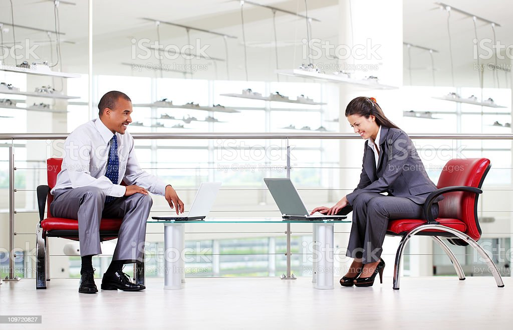 Business people typing on laptop computers in workplace. stock photo