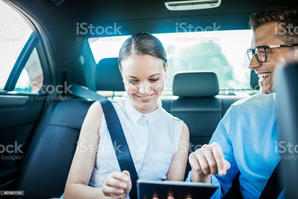 Business people using a tablet in a car stock photo