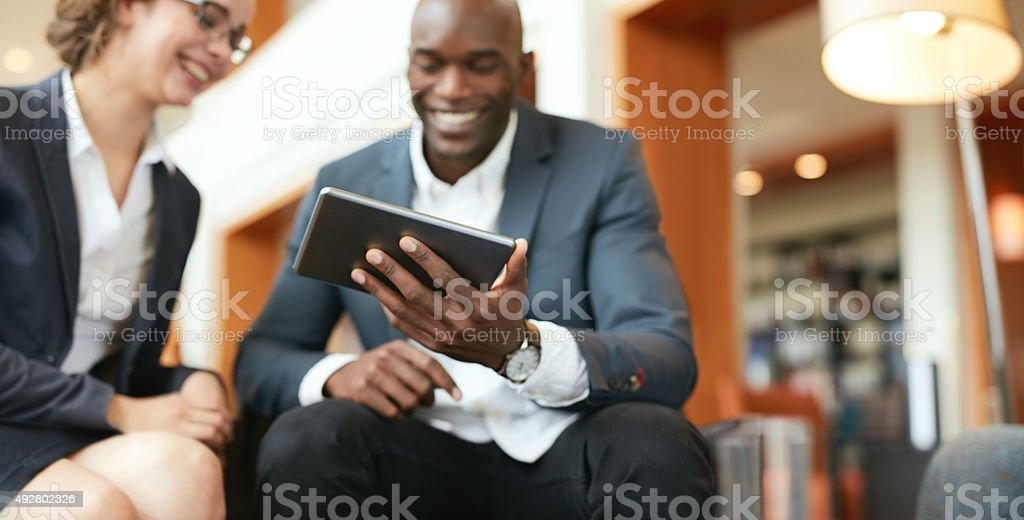 Business people using digital tablet at hotel lobby stock photo