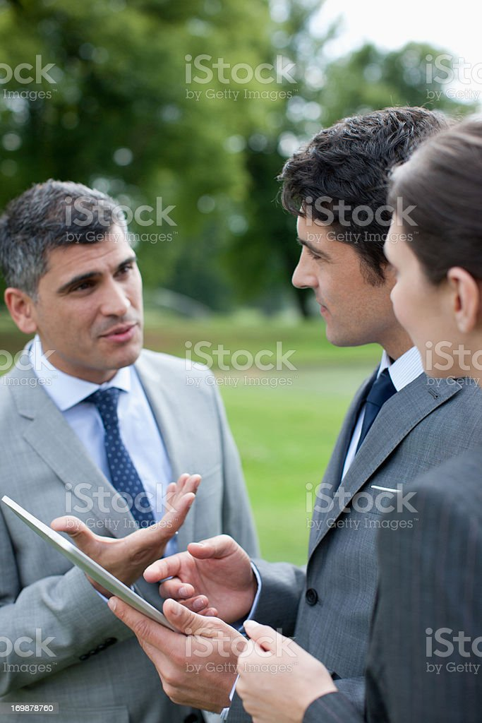 Business people using digital tablet together outdoors royalty-free stock photo